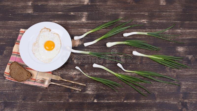 鸡蛋、香葱和黑色的盘子 免版税库存图片