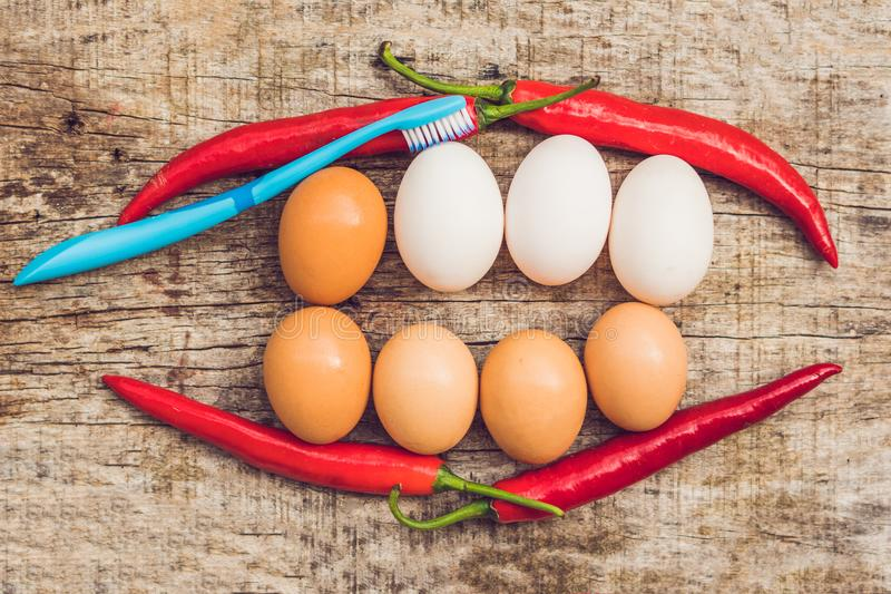 鸡蛋和红辣椒以一张嘴的形式与牙 白鸡蛋是被漂白的牙 黄色鸡蛋-在漂白的前 牙漂白 免版税库存图片