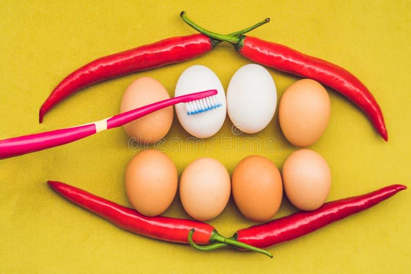 鸡蛋和红辣椒以一张嘴的形式与牙 白鸡蛋是被漂白的牙 黄色鸡蛋-在漂白的前 牙漂白 免版税库存照片