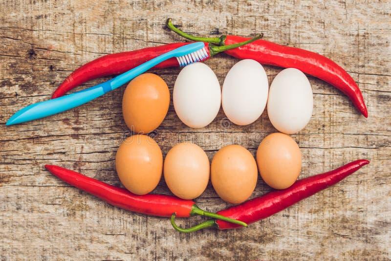 鸡蛋和红辣椒以一张嘴的形式与牙 白鸡蛋是被漂白的牙 黄色鸡蛋-在漂白的前 免版税库存照片