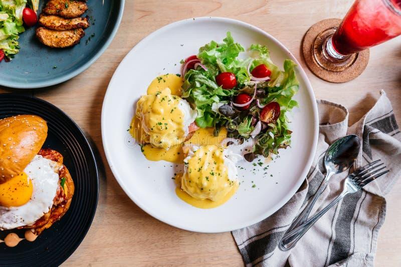 鸡蛋本尼迪克特顶视图服务用在白色板材的沙拉在可口早餐和早午餐的木桌上 免版税图库摄影