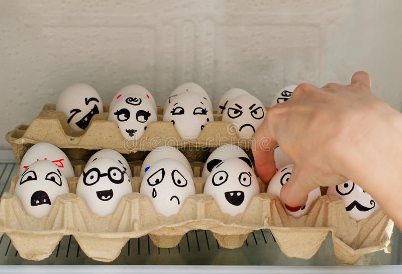 鸡蛋激动在冰箱的被绘的,一只女性手采取他们中的一个 免版税库存照片