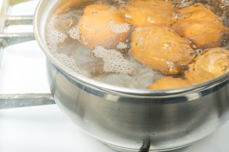 鸡蛋煮沸在水中 有产品的平底锅在煤气炉 图库摄影