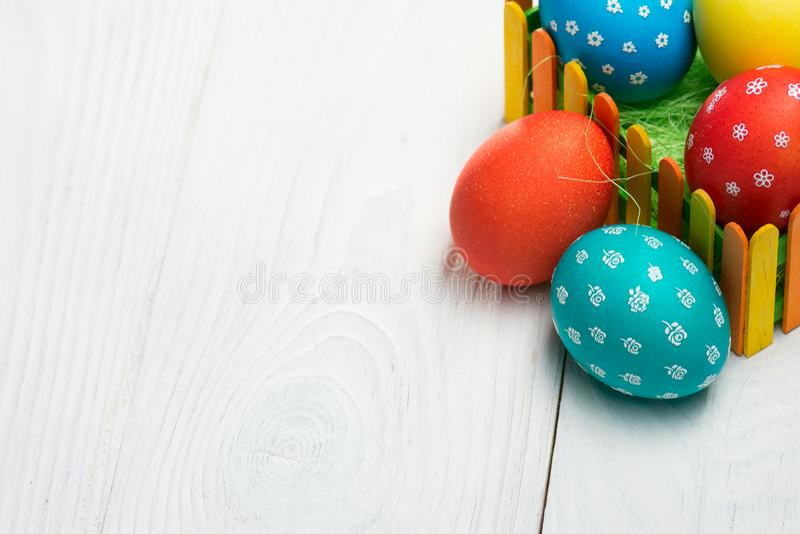 鸡蛋的构成复活节的在一张木桌上的五颜六色的篱芭后 免版税库存图片