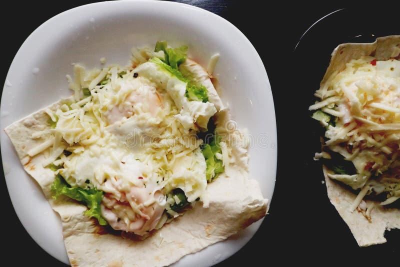 鸡蛋盘  荷包蛋用皮塔饼面包、莴苣和乳酪在一个白色和黑色的盘子 免版税库存照片