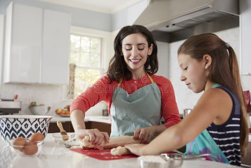 鸡蛋面包面包的犹太母亲和女儿辗压面团 免版税库存照片