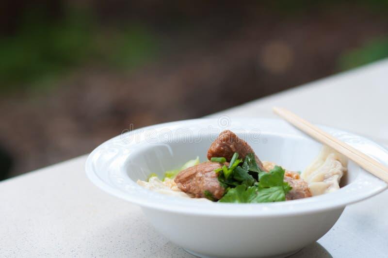 鸡蛋面用可口被炖的猪肉和饺子 免版税图库摄影
