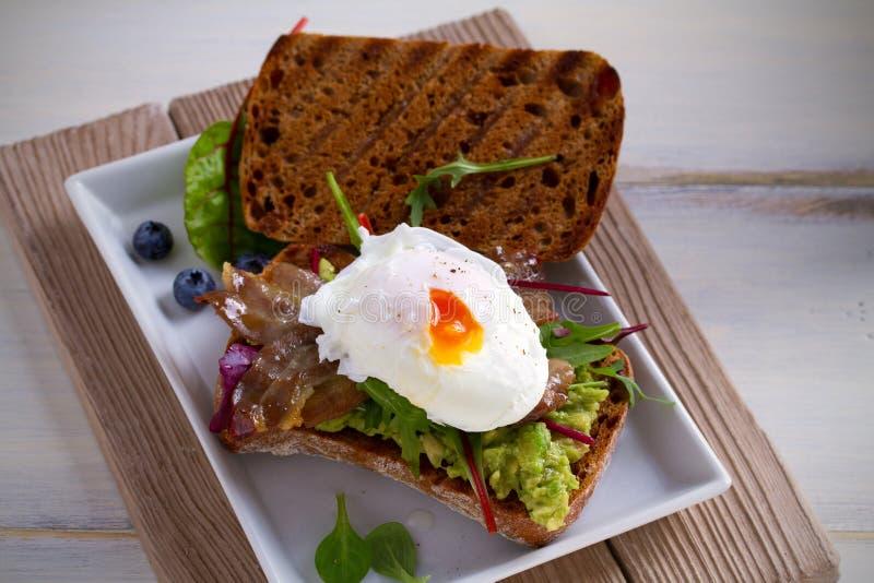 鸡蛋,烟肉,捣毁了白豆和鲕梨在多士三明治 免版税图库摄影
