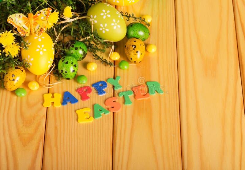 鸡蛋,糖果,花,蝴蝶,词在光的复活节快乐求爱 免版税库存图片
