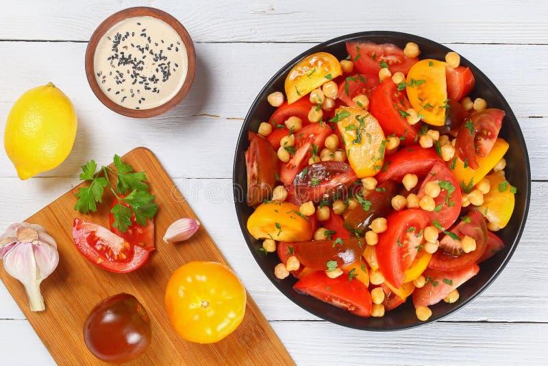 鸡豆在黑碗的蕃茄沙拉 库存照片
