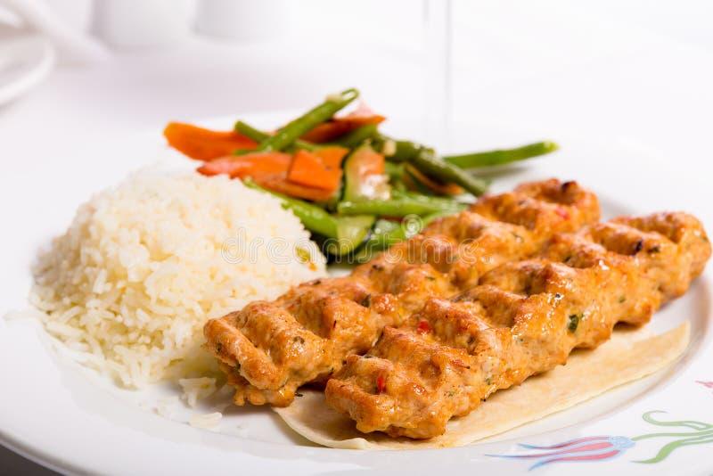 鸡阿达纳Kebap服务与米肉饭菜和红色vi 免版税库存图片