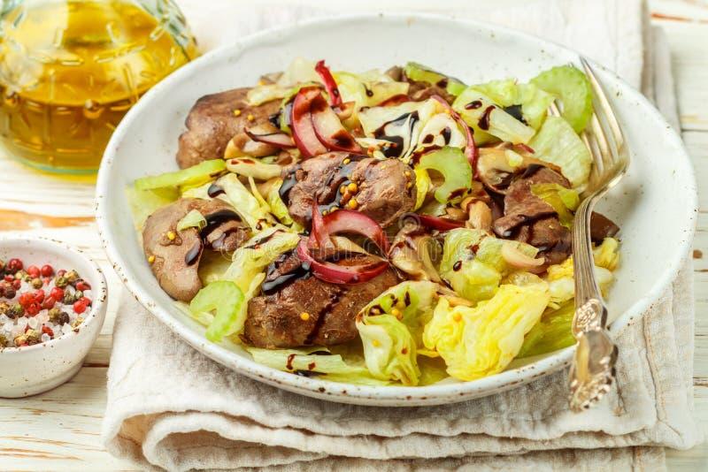 鸡鸭子、鹅、兔子肝脏、卷心莴苣、红洋葱、芹菜和油煎的蘑菇温暖的沙拉与选矿 库存照片