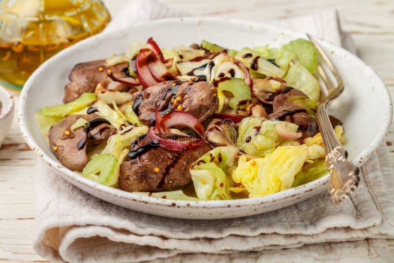 鸡鸭子、鹅、兔子肝脏、卷心莴苣、红洋葱、芹菜和油煎的蘑菇温暖的沙拉与选矿 库存图片