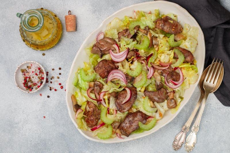 鸡鸭子、鹅、兔子肝脏、卷心莴苣、红洋葱、芹菜和油煎的蘑菇温暖的沙拉  图库摄影