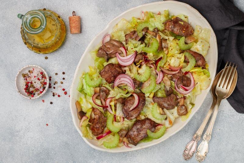 鸡鸭子、鹅、兔子肝脏、卷心莴苣、红洋葱、芹菜和油煎的蘑菇温暖的沙拉  库存图片