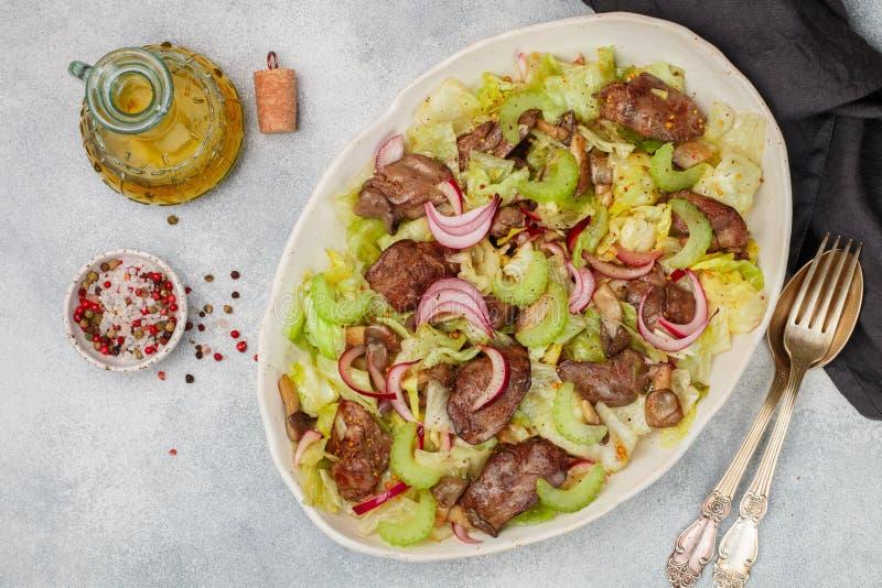 鸡鸭子、鹅、兔子肝脏、卷心莴苣、红洋葱、芹菜和油煎的蘑菇温暖的沙拉  免版税图库摄影