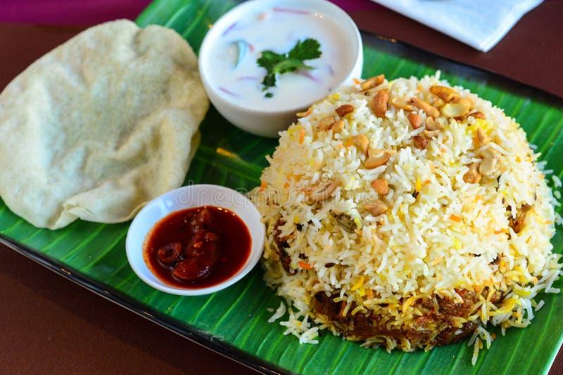 鸡biryani thali服务用凝乳和papad 免版税库存图片