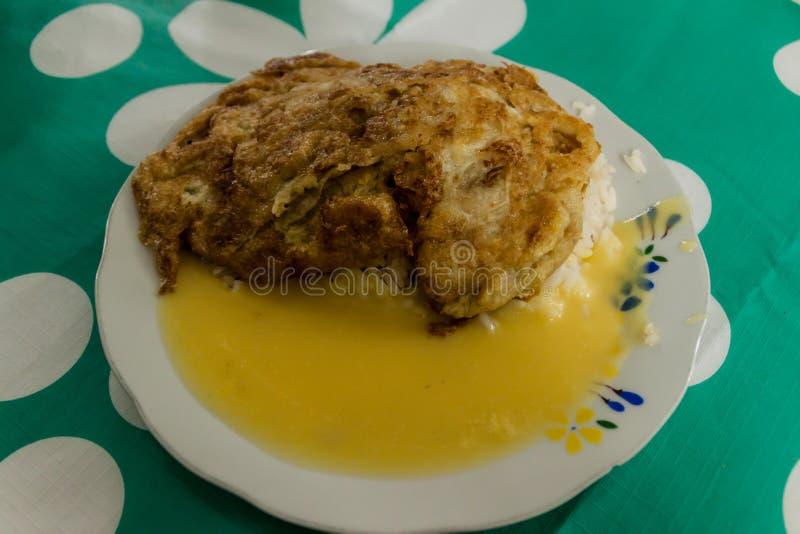 鸡milanesa在一家小地方餐馆在牛排上添面包用米和调味汁在Leimebamba,Pe 免版税库存照片