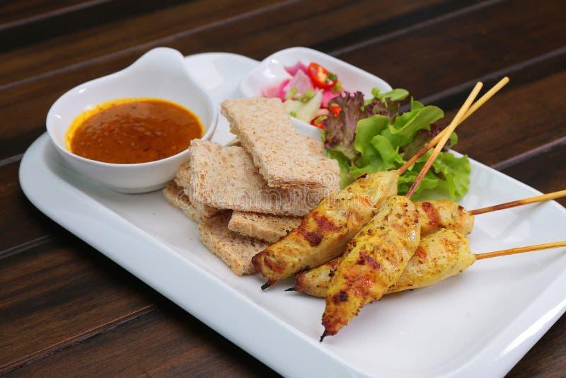 鸡Satay服务用花生调味汁和面包,亚洲串 免版税库存照片