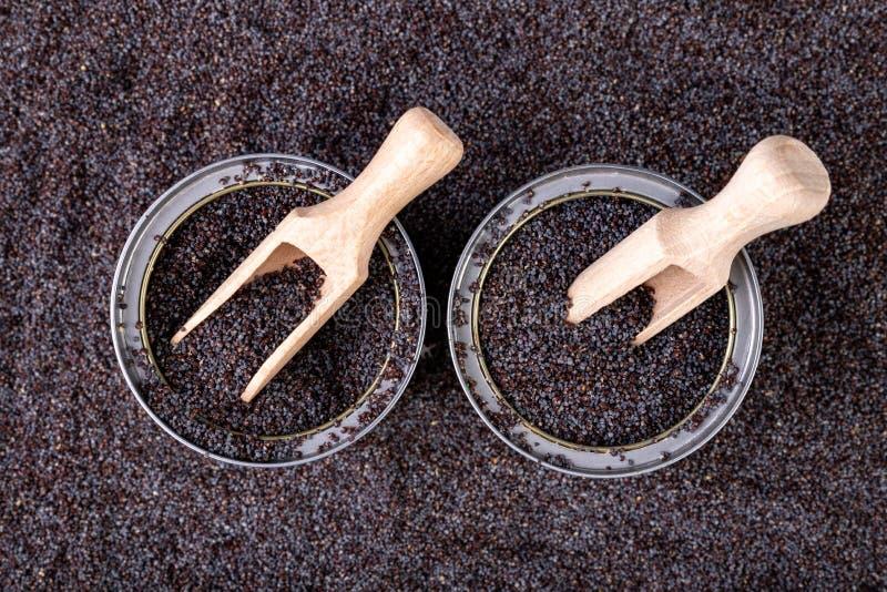 鸦片五谷在一个罐头的在厨房用桌上 溢出的罂粟种子和木匙子在贮存货柜 免版税库存照片