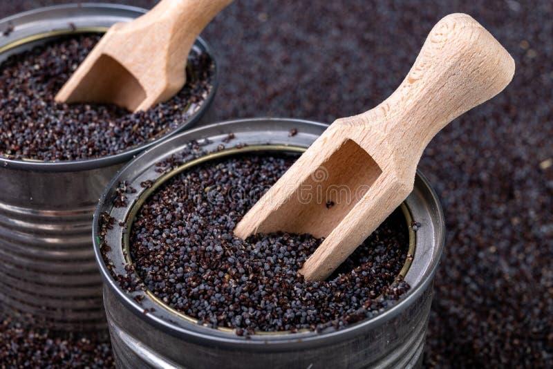 鸦片五谷在一个罐头的在厨房用桌上 溢出的罂粟种子和木匙子在贮存货柜 免版税图库摄影