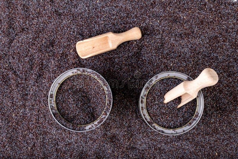 鸦片五谷在一个罐头的在厨房用桌上 溢出的罂粟种子和木匙子在贮存货柜 免版税库存图片