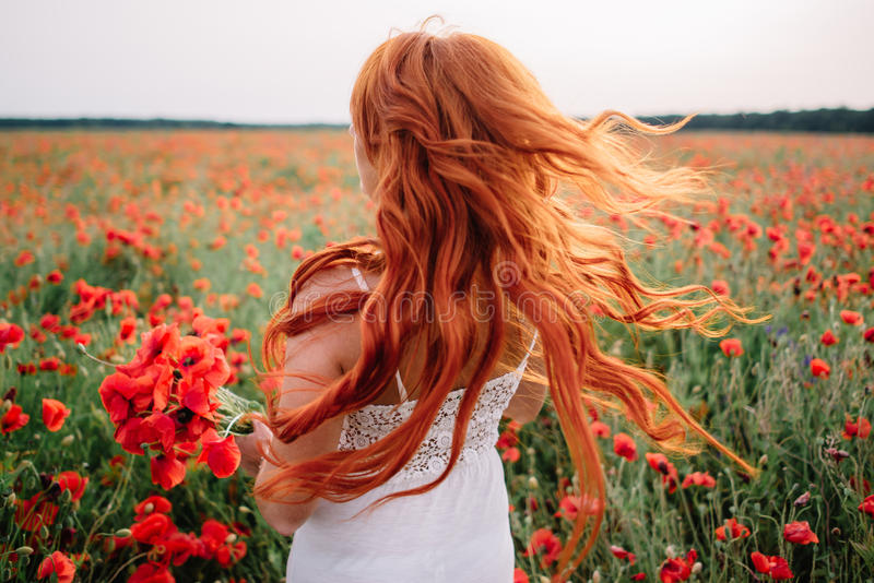 鸦片领域的美丽的年轻红发妇女与飞行头发 免版税库存图片