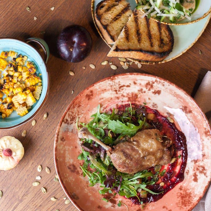 鸭子腿confit、烤玉米和鲭类rillette用黄瓜沙拉用多士 免版税图库摄影
