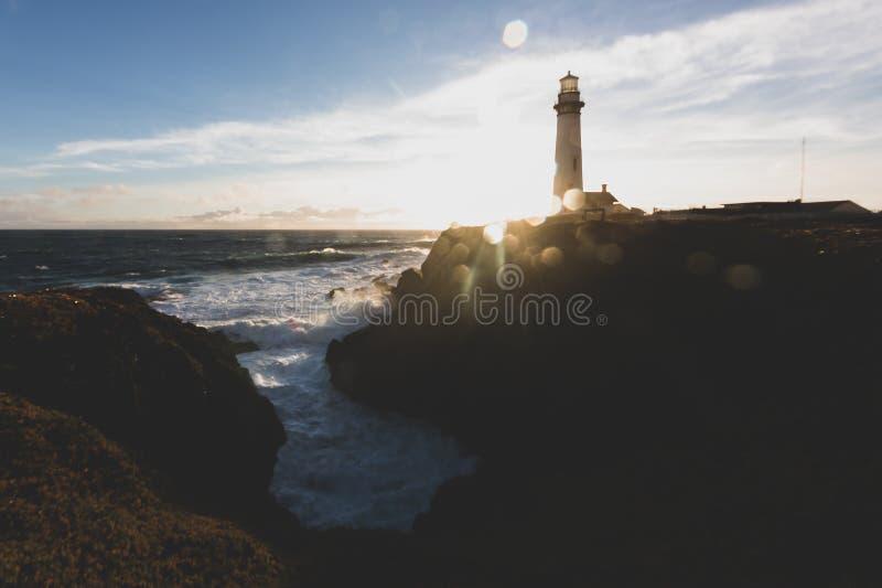鸽子在加利福尼亚北部太平洋海岸线的点灯塔在与一片艺术性的太阳火光的日落,葡萄酒神色之前 免版税库存图片