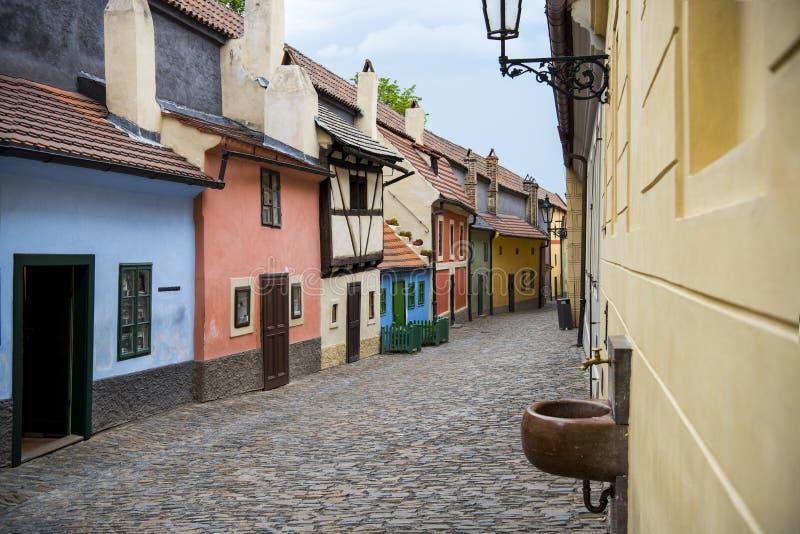 鹅卵石街道和叫作在城堡墙壁布拉格捷克稀土里面的金黄车道的工匠五颜六色的16世纪村庄  免版税库存照片