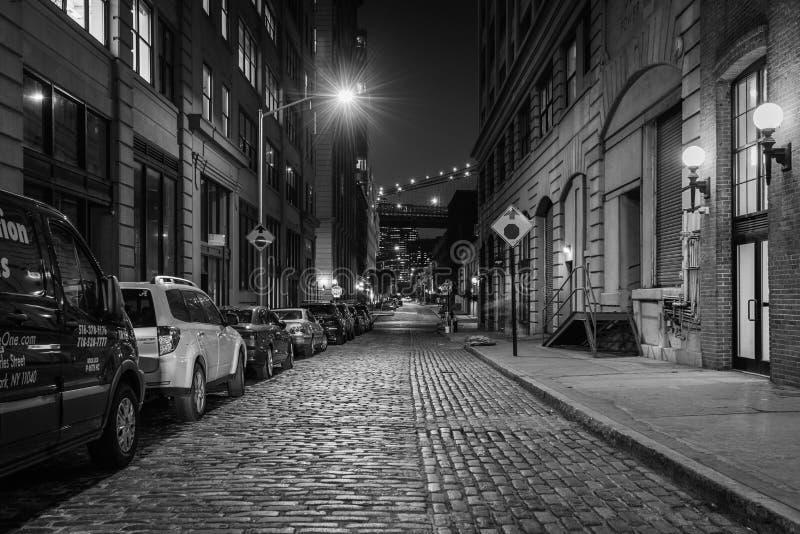 鹅卵石街道在DUMBO,布鲁克林,纽约的晚上 库存照片