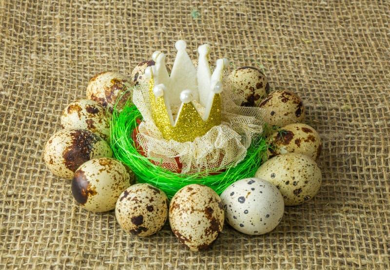 鹌鹑蛋冠在圈子在塑料蓝色碗在一张木桌上的红色盐附近 库存图片