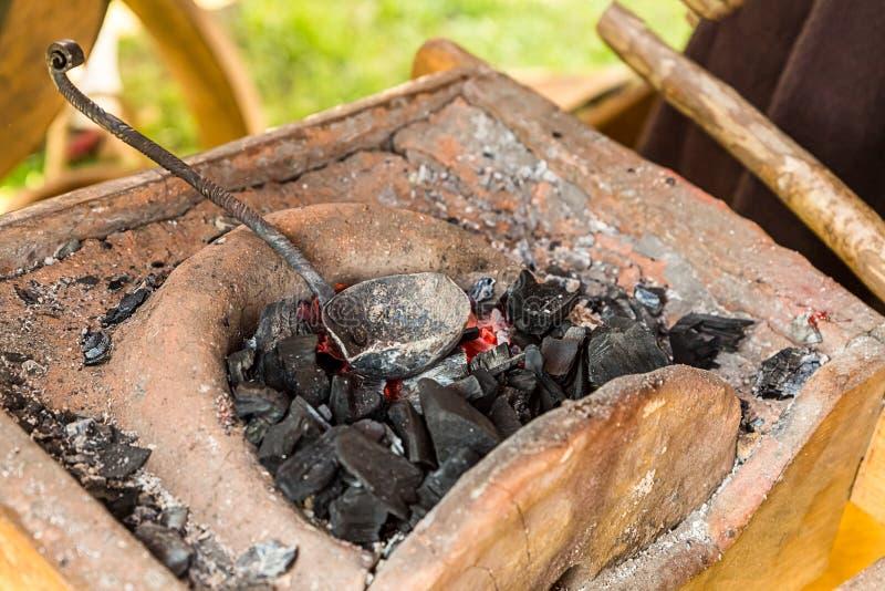 鹰铁匠熔化加热的金属燃烧煤炭红色伪造的匙子桶的武器的垫铁生产 库存照片