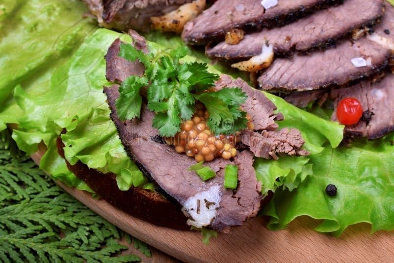 麋肉被烘烤的火腿被切成切片冠上与绿叶和蔓越桔 免版税图库摄影