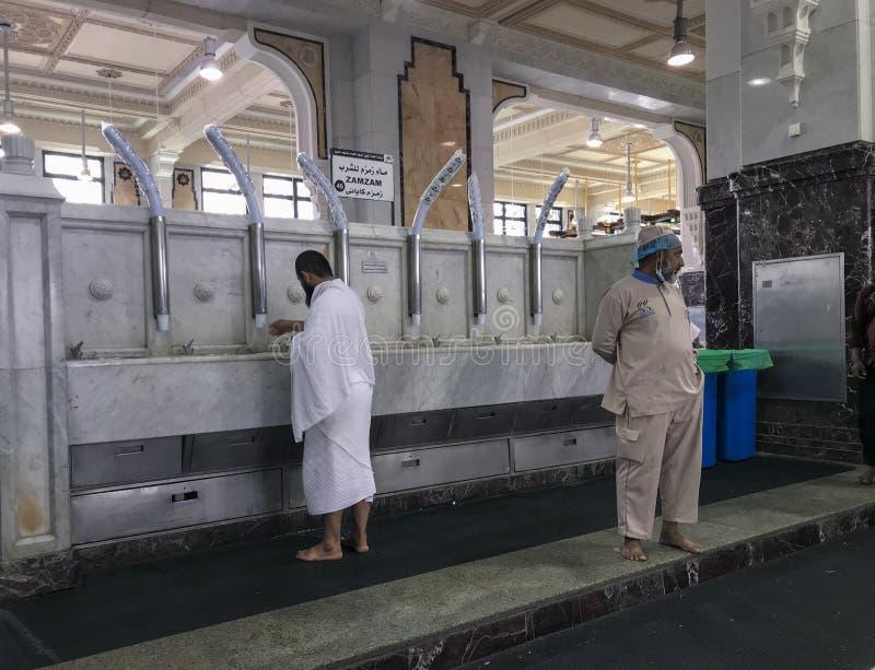 麦加,沙特阿拉伯- 2019年6月4日:当ihram白色衣裳的一个回教香客喝zamzam水里面时,工作者看  图库摄影