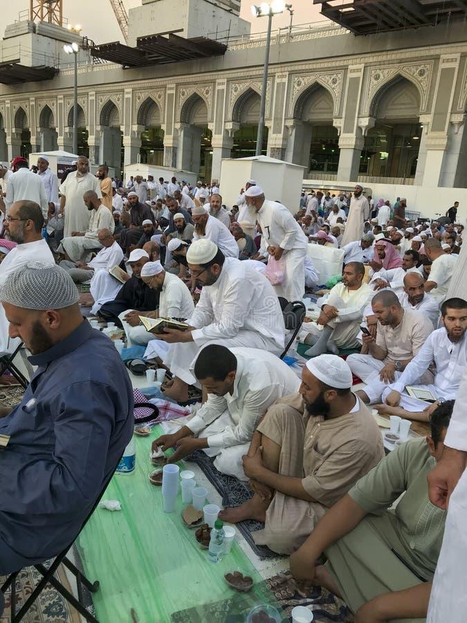 麦加,沙特ARABIA-CIRCA 2019年6月:身份不明的回教人读了古兰经和提议祷告,当等待断裂快速的里面时 库存照片