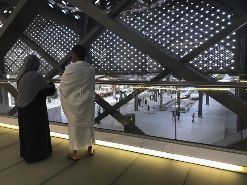 麦地那,沙特阿拉伯- 2019年5月27日:一对回教夫妇俯视在轨道的高速火车在HSR Madinah驻地在麦地那,沙特 免版税图库摄影