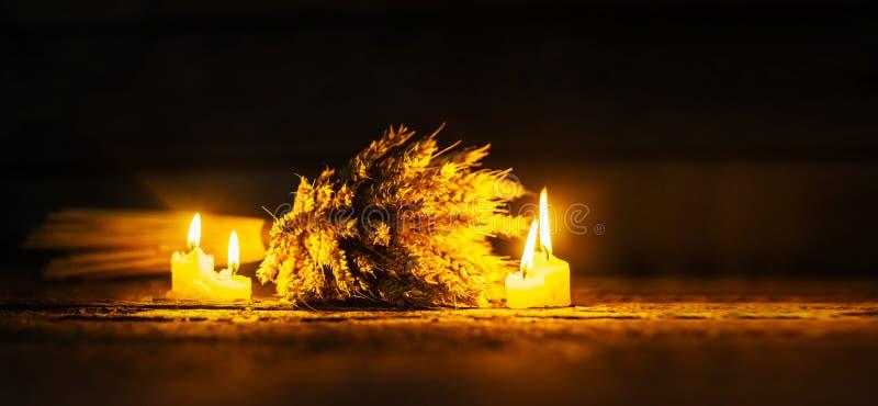 麦子和照明设备蜡烛的耳朵在黑暗的木背景的 免版税库存图片