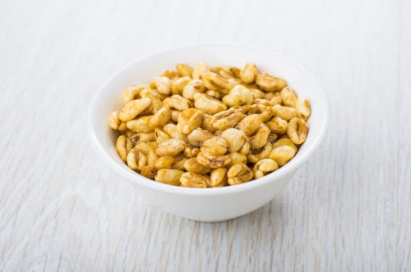 麦子用在白色碗的蜂蜜在木桌上 免版税库存图片