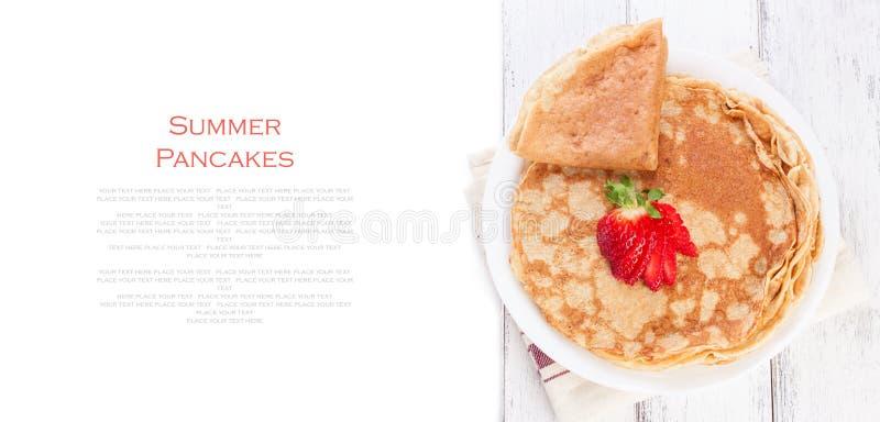 麦子金黄酵母薄煎饼或绉纱钉书针,传统在俄国薄煎饼星期,用在一张木桌上的新鲜的草莓 图库摄影