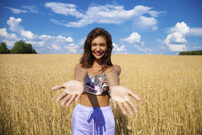 麦子金黄领域的愉快的少妇 免版税库存图片