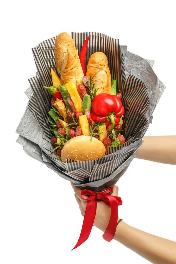 麦子面包、芝麻不同的品种小圆面包、乳酪,香肠和胡椒在灰色纸在男性ha被包裹作为礼物花束 库存图片