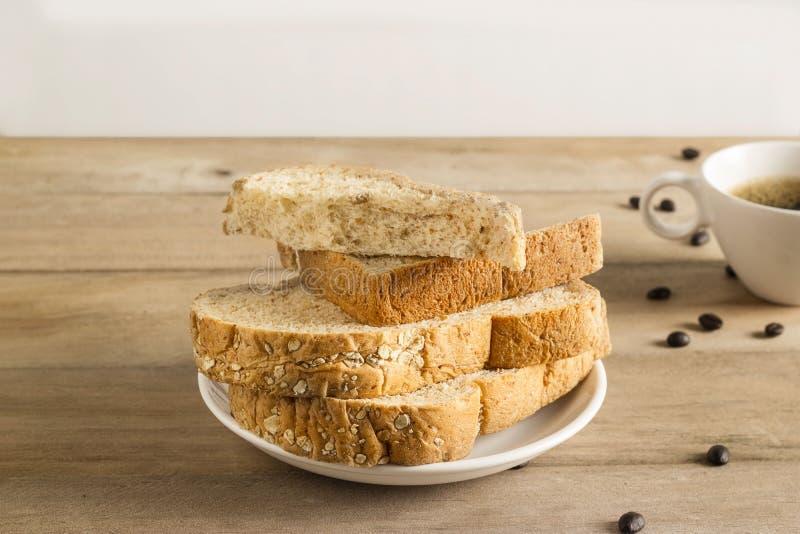 麦子面包用白色芝麻、咖啡豆和咖啡杯 免版税库存照片