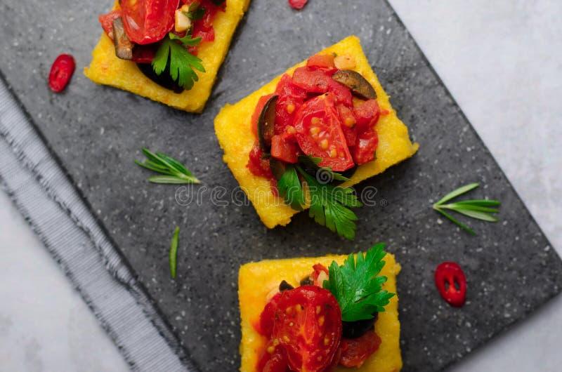 麦片粥叮咬用的蕃茄和冠上的黑橄榄,麦片粥开胃菜,可口快餐 免版税库存图片