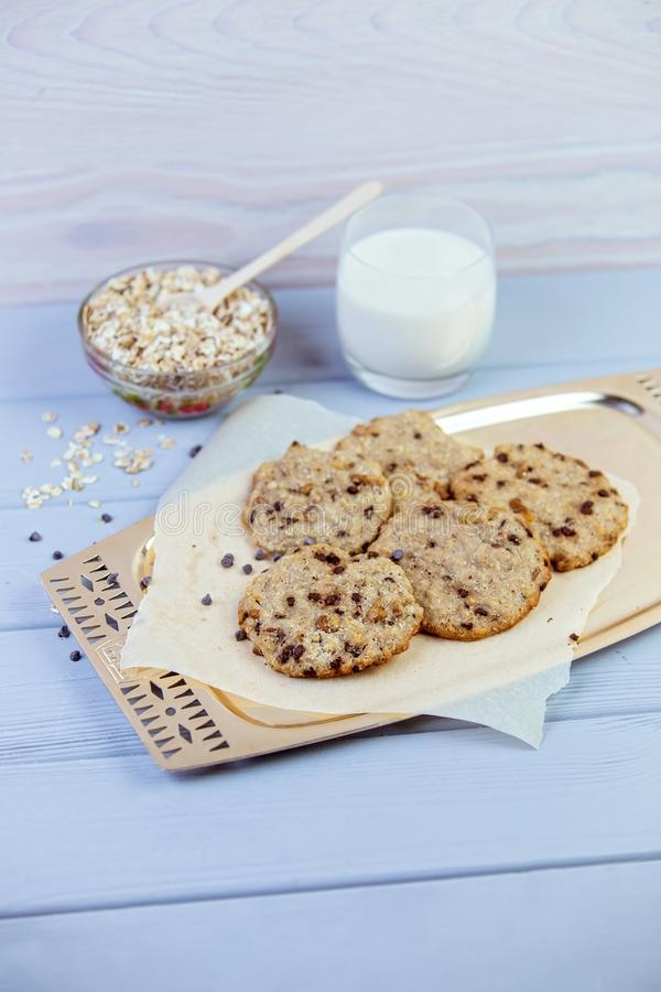 麦甜饼用干果子,种子,在电线支架的蔓越桔 在与一杯的木灰色背景新鲜的温暖的牛奶 库存照片