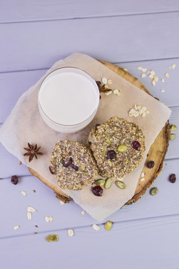 麦甜饼用干果子,种子,蔓越桔 在与一杯的木灰色背景新鲜的温暖的牛奶 舒适静物画 免版税库存照片