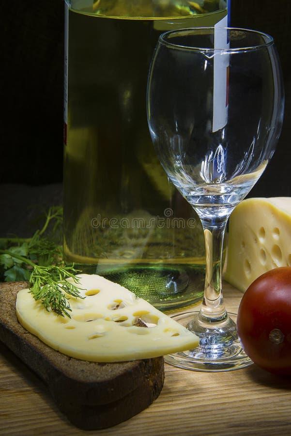 黑麦面包用乳酪、酒瓶和空的玻璃 库存图片