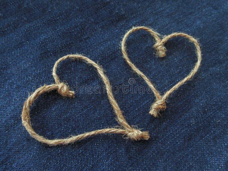 麻线的标志两心脏在牛仔布的 库存照片