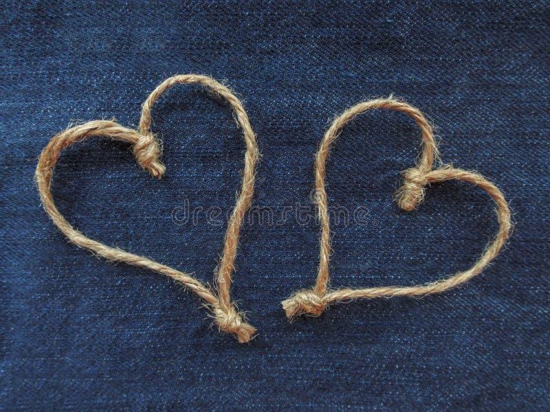 麻线的标志两心脏在牛仔布的 免版税库存图片