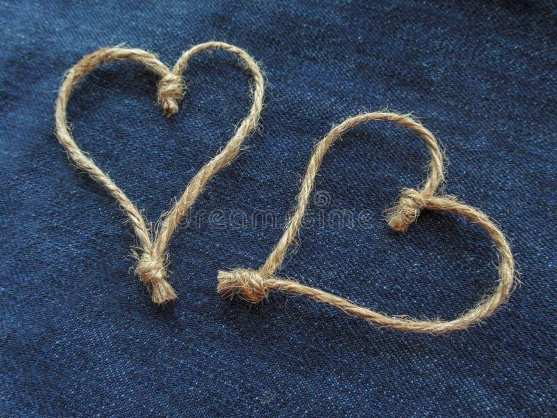麻线的标志两心脏在牛仔布的 免版税图库摄影